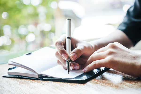 Stock photo of person writing in their journal.